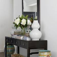 Black Gloss Console Table Seagrass Baskets Tucked Under Clear Acrylic Console Table