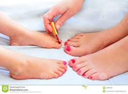 mother and child paint their feet with nail polish stock photo