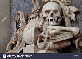 ornamental carved skull with bones leaf sprigs and books situated