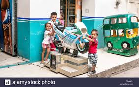4 smiling young mexican children pose outside shop with suzuki