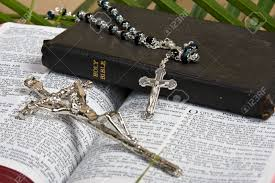 close up of silver rosary and crucifix on bible with palm leaves