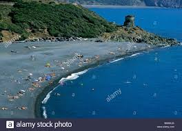 sunbathers on a black sand beach cape corse corsica france