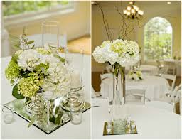 modern wedding reception flower arrangements lined up around an