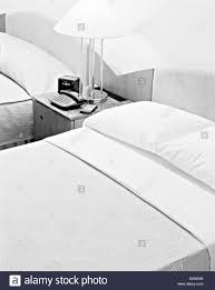 beds in a hotel room black and white nightstand clock flowers
