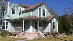 day static two story blue green wood house that sits corner it has