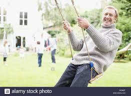 senior man swinging in backyard with family stock photo royalty