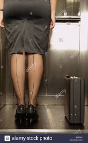 rear view of businesswoman with seamed stockings standing in