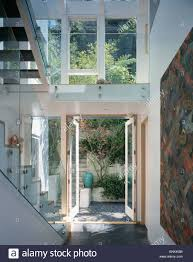 large double height modern hall with glass banister on staircase