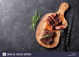 meat cutting table tops grilled sliced beef steak on cutting board over stone table top