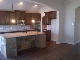 dark walnut stained knotty alder cabinets travertine backsplash