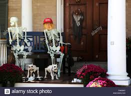a donald trump mask on a halloween skeleton decoration outside a