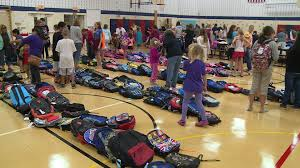 local families in need receive backpacks with supplies