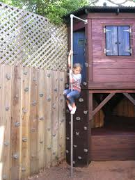 fire pole and rock climbing wall extends onto fence playhouses