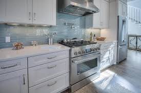 white beach house kitchen with linear glass backsplash tiles