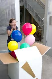 birthday balloons in a box someone with a boxful of helium filled balloons or a