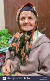 old berber woman with face tattoos selling vegetables in the