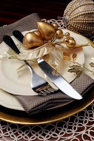 gold theme christmas dinner table setting close up on cutlery and