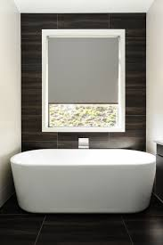 stunning bath feature with dark wood look tiles extending from the