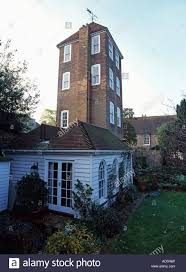 tall tower converted into house with single storey white timbered