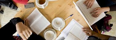 writing college paper writing lab grinnell college coffee cups books pens and paper are strewn around a table