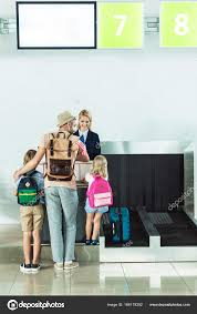 family at check in desk at airport u2014 stock photo