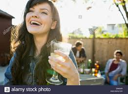 laughing woman drinking wine at backyard barbecue stock photo