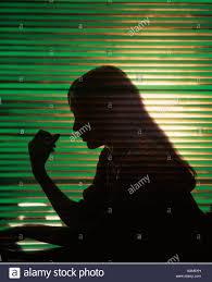 1970s worried woman profile silhouette against green window