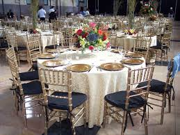 gold chiavari chairs with a gold tablecloth and gold plates for a