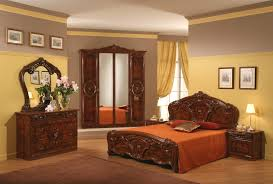 carving brown varnished wooden bed with orange blanket and pillow