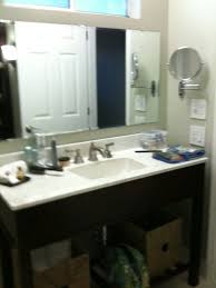 bathroom sink and counter top magnifying mirror old window above