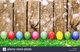 wooden easter eggs that open easter eggs in green grass on wooden background with light leaks