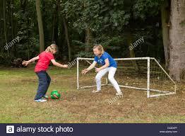 two young girls playing soccer in backyard garden stock photo