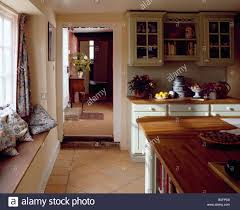 cushions on windowseat of country kitchen with terracotta tiled