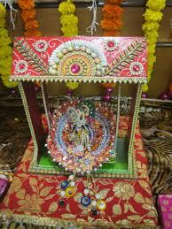 lord krishna sitting on the decorated swing on the janmashtami