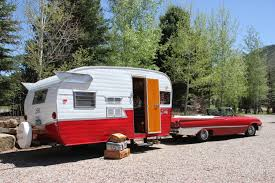 retro road trip with a vintage travel trailer towed by a classic