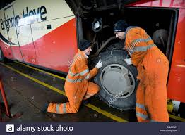 two mechanics fitting snow chains to a bus wheel using a bus stock photo two mechanics fitting snow chains to a bus wheel using a bus garage inspection pit
