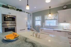a white craftsman kitchen with sea pearl green quartzite