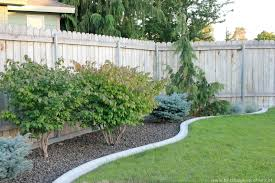 backyard gardens and light brown stone garden edging and green