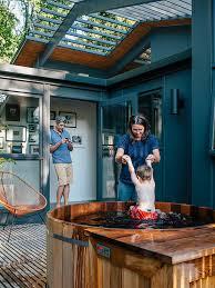 tub nestled in wood deck in midcentury portland home garden