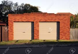 two garage doors red brick wall evening light stock photo