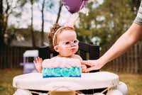 baby in highchair wearing ice cream cone headband stock photo offset