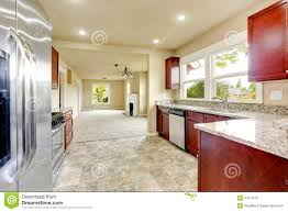 bright kitchen room with granite tops and burgundy cabinets stock