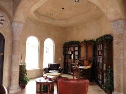 mediterranean home office with high ceiling u0026 arched window in