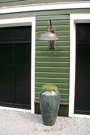 barn style post lights estled in between the barn style garage doors is a large gooseneck