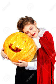 cool teen boy in a costume of vampire posing with pumpkin with