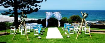 beachside garden wedding ceremony folding white americana chairs