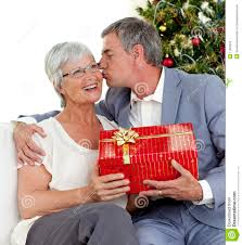 man giving a kiss and christmas gift to his wife royalty free