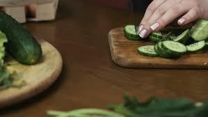 woman slicing cucumber female hands cut green cucumber rings big