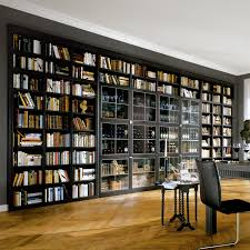 tall black wood bookshelf with glass sliding doors on red wall