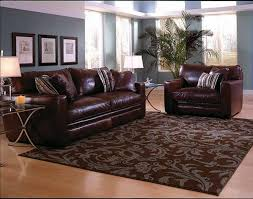 sitting room curved black sofa circular rugs living brown and